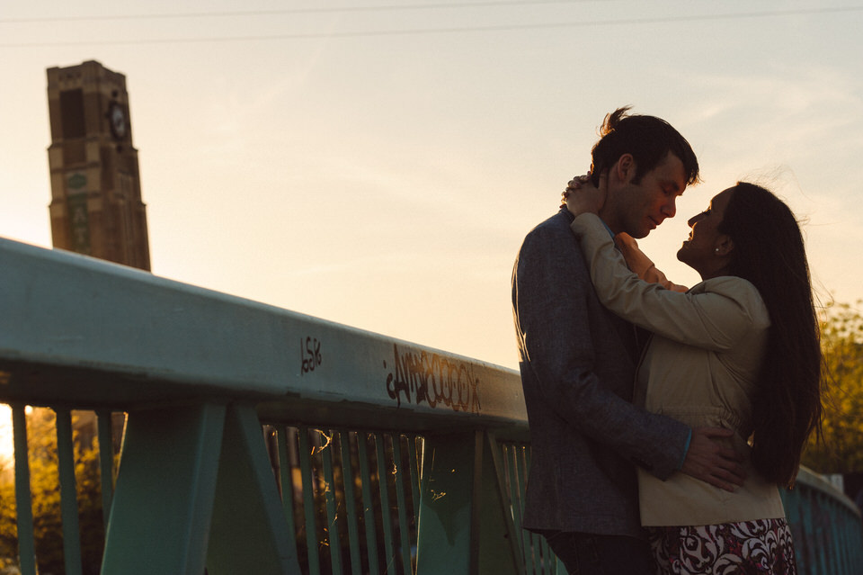 Couple on a bridge at sunset with the Atwater Tower behind them