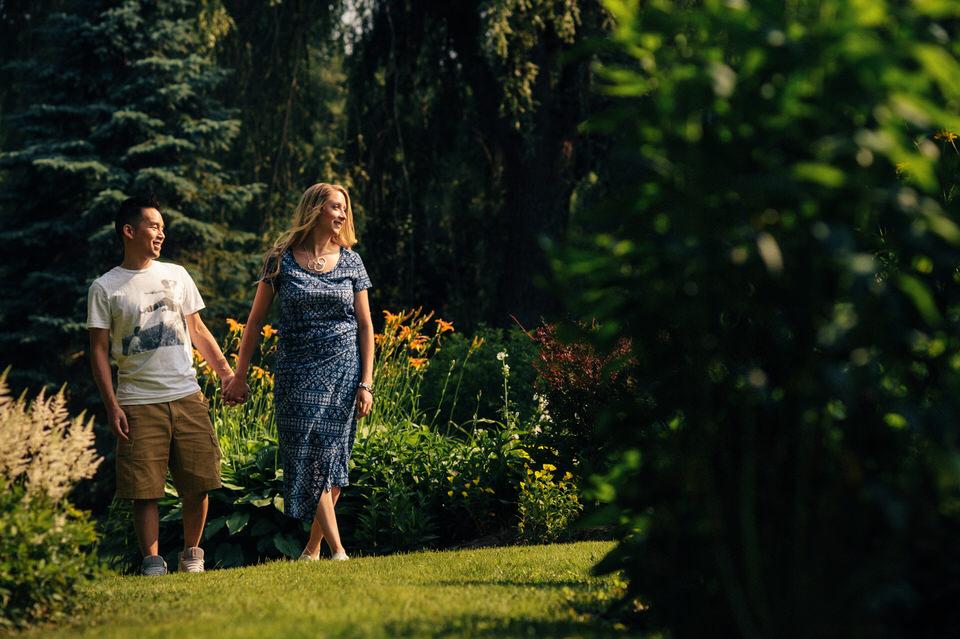 Engaged couple walking in a backyard garden