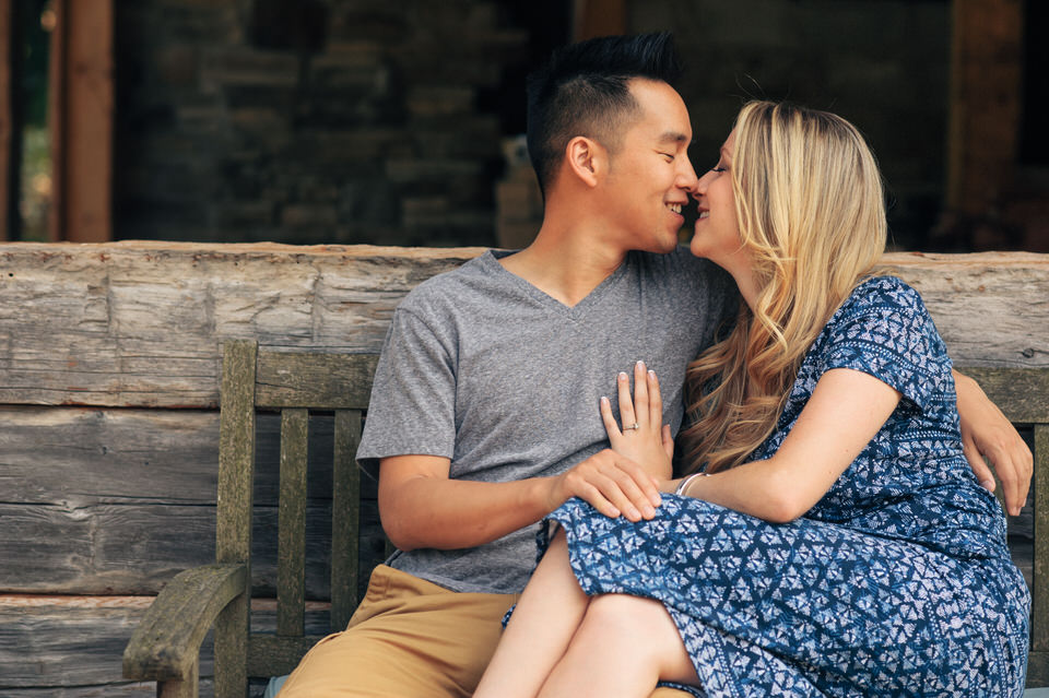 Engagement photo of couple cuddling on a wooden bench
