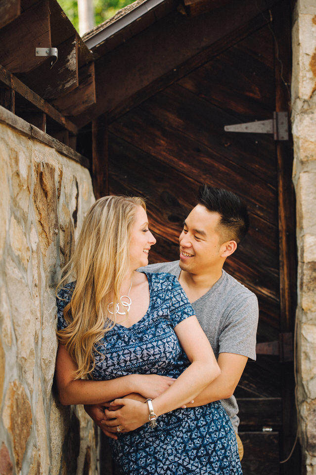 Engaged couple hugging and leaning on stone wall in backyard