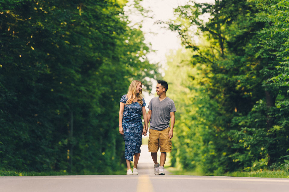 Engaged couple walking hand in hand on a country road