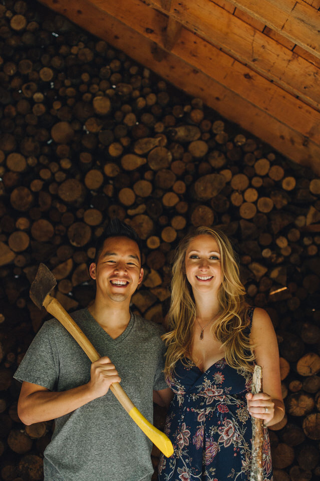 Silly engagement portrait with hatchet in cabin