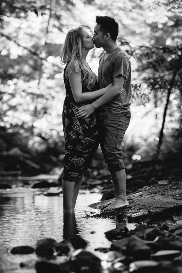 Couple kissing on the banks of a creek in the woods