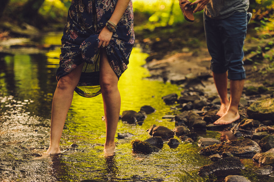 Feet of engaged couple crossing a creek