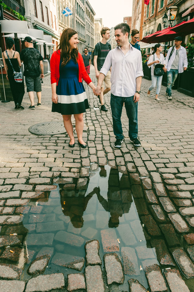 Couple holding hands with reflection in puddle