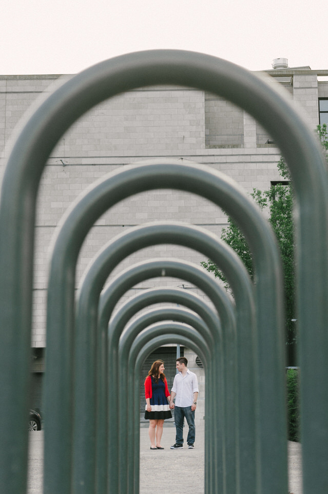 Engagement portrait of couple framed by row of bicycle racks