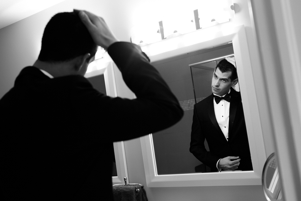 Groom fixing his hair in the mirror