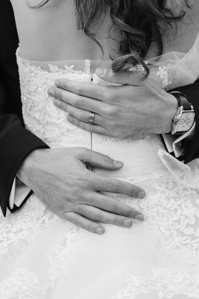 Close up of groom's hands on bride's back