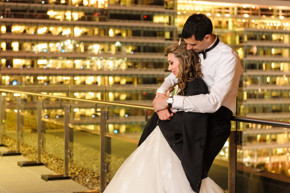 Wedding couple taking a break on the terrace during night time reception