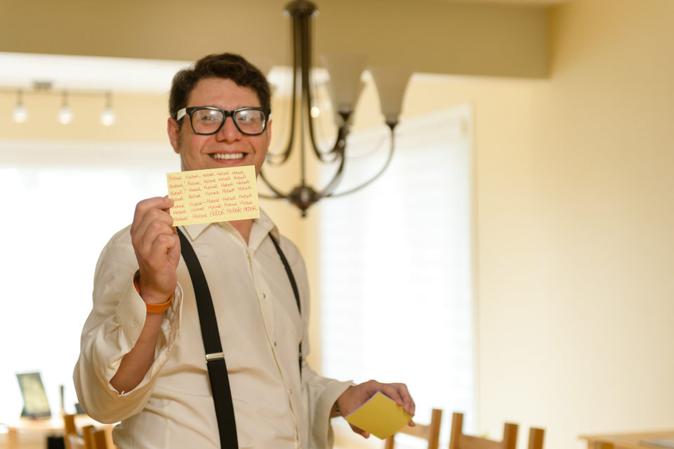 "Groom holding an index card that reads ""Hodor Hodor Hodor Hodor..."""