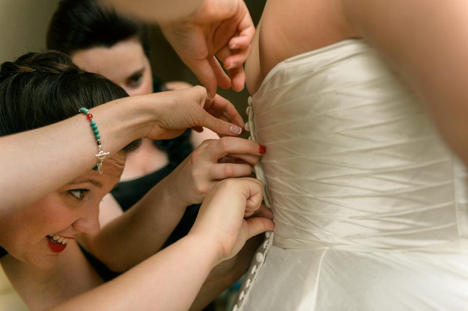 Friends helping bride do up her dress buttons