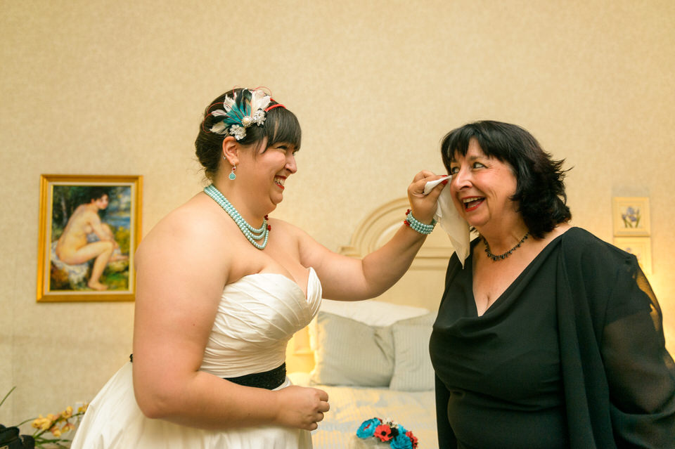 Bride wiping her mom's eyes with handkerchief as they laugh together