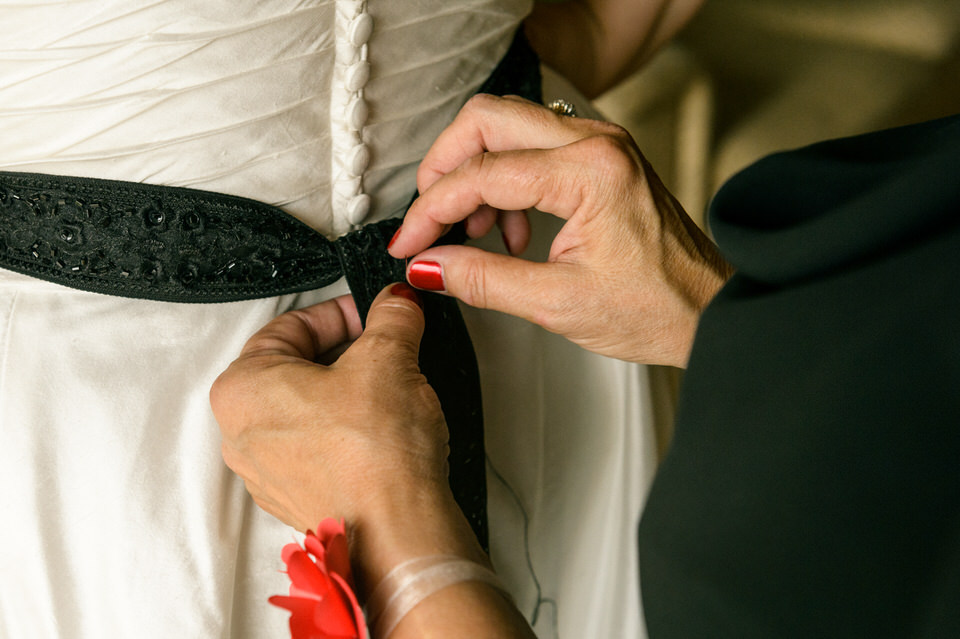 Mother sewing bride's wedding sash onto her