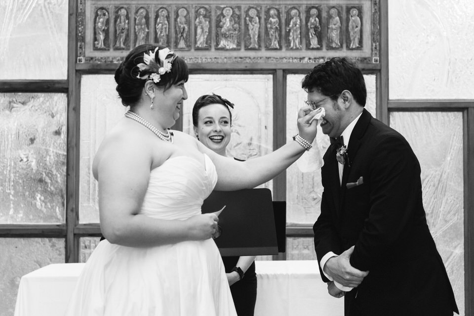 Bride wiping the groom's eyes during wedding ceremony