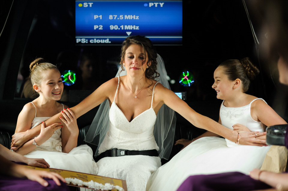Bride holding her flower girls safely in the limo with no seat belts