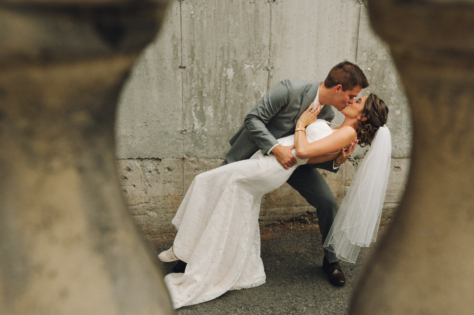 Wedding couple dipping for a kiss and framed by balusters