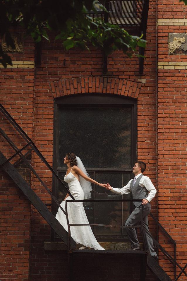 Wedding couple climbing fire escape at Chateau Saint-Ambroise