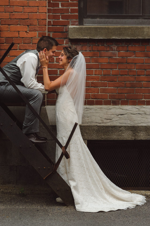 Groom sitting on fire escape and kissing bride standing in front of him