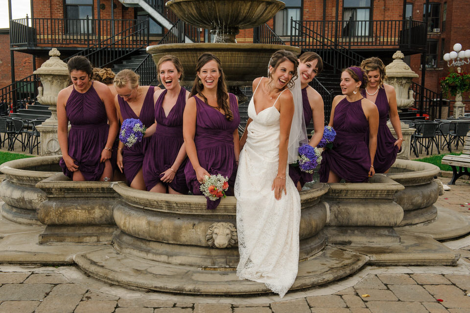 Bridesmaids and bride standing in a fountain