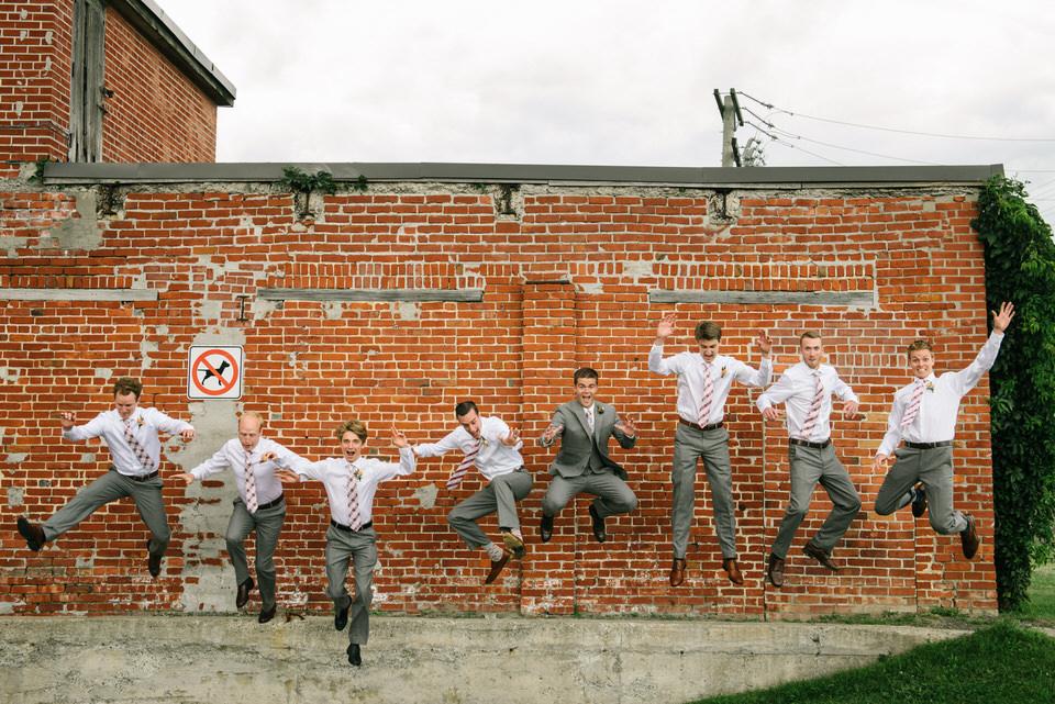 Groomsmen jumping off a wall