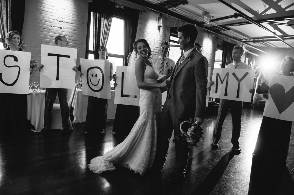 Wedding couple enters the reception while their wedding party holds signs