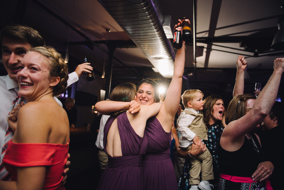 Bridesmaid raising her beer bottle
