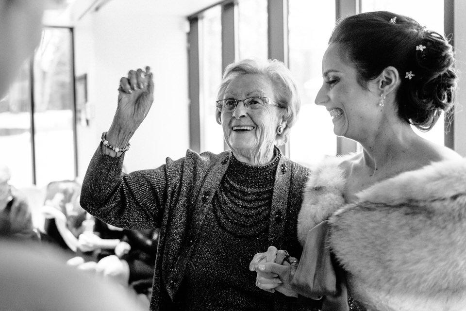 Grandmère excitée qui tient la main de la mariée