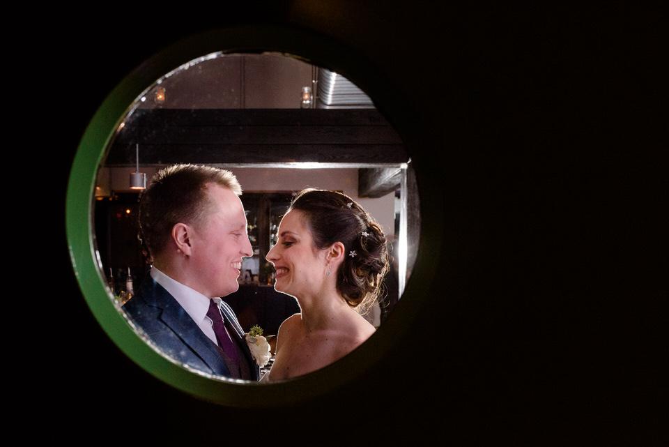 Portrait des mariés par la fenêtre ronde d'une porte