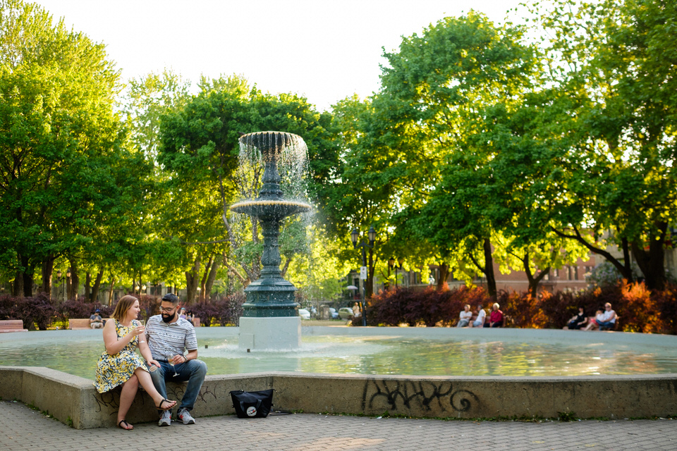 Newly engaged couple sitting on side of fountain in Saint-Louis square
