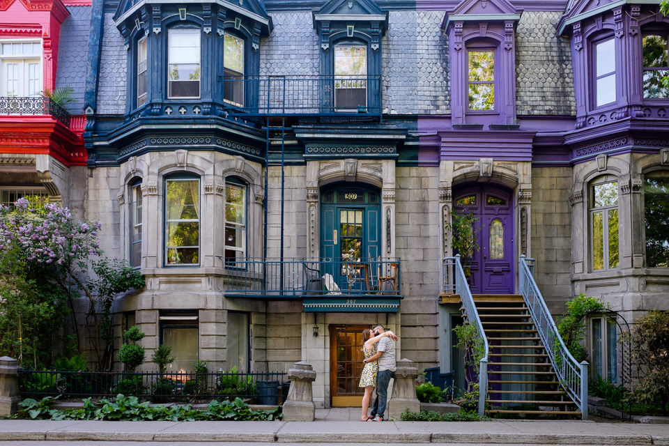Engagement portrait in front of colourful painted houses in Plateau Mont-Royal neighbourhood