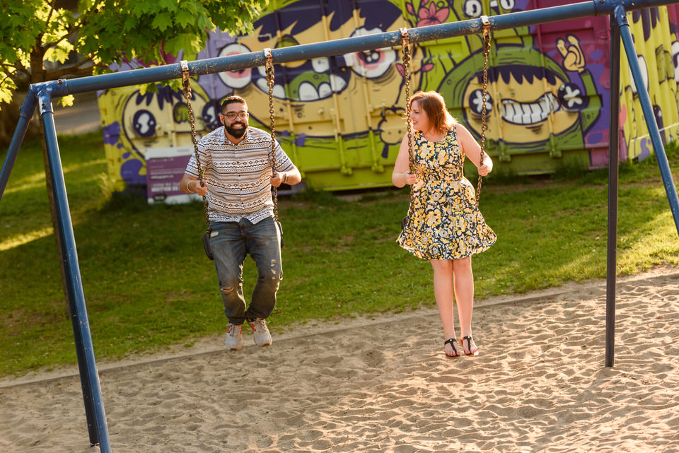 Couple swinging on a swing set in playground