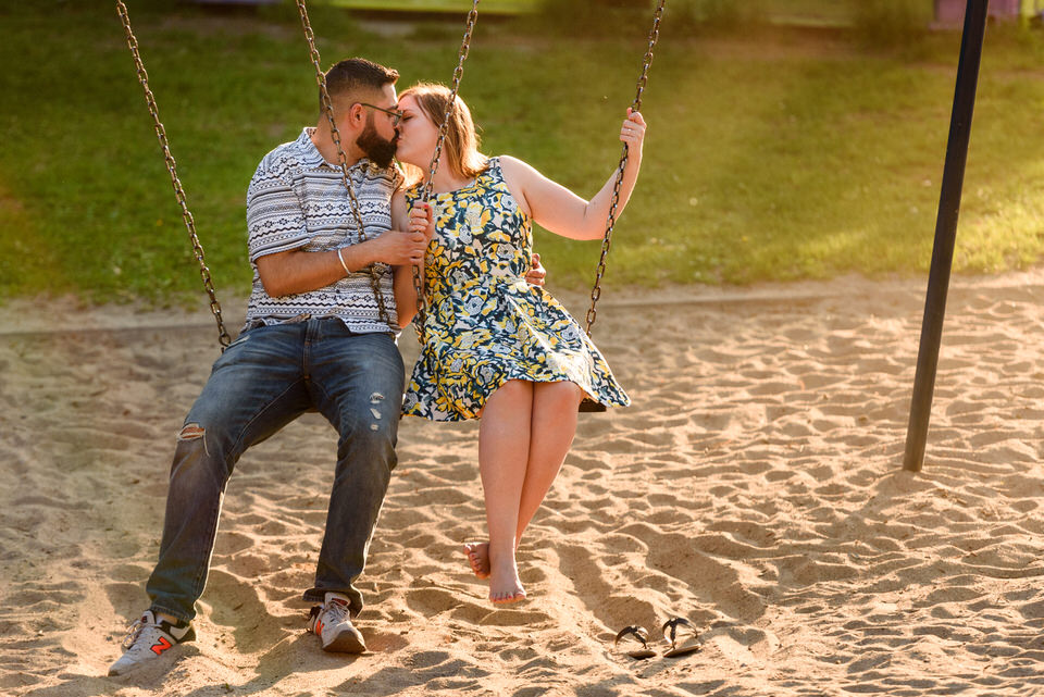 Engagement photo on a swing set at playground at sunset