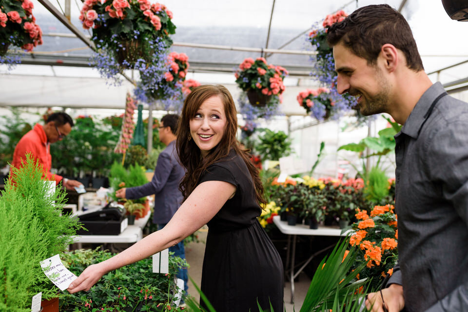 Woman looking at plant and laughing at her fiance