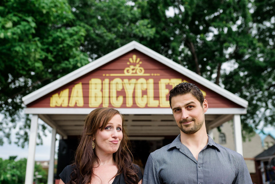 Engaged couple making silly faces in front of a bicycle shop
