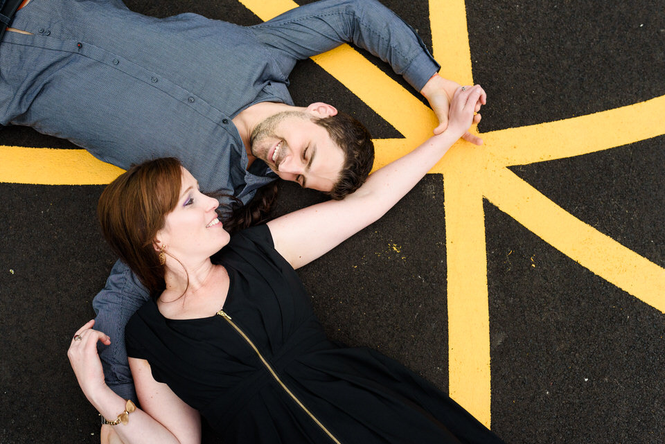 Couple lying on concrete with yellow lines near them