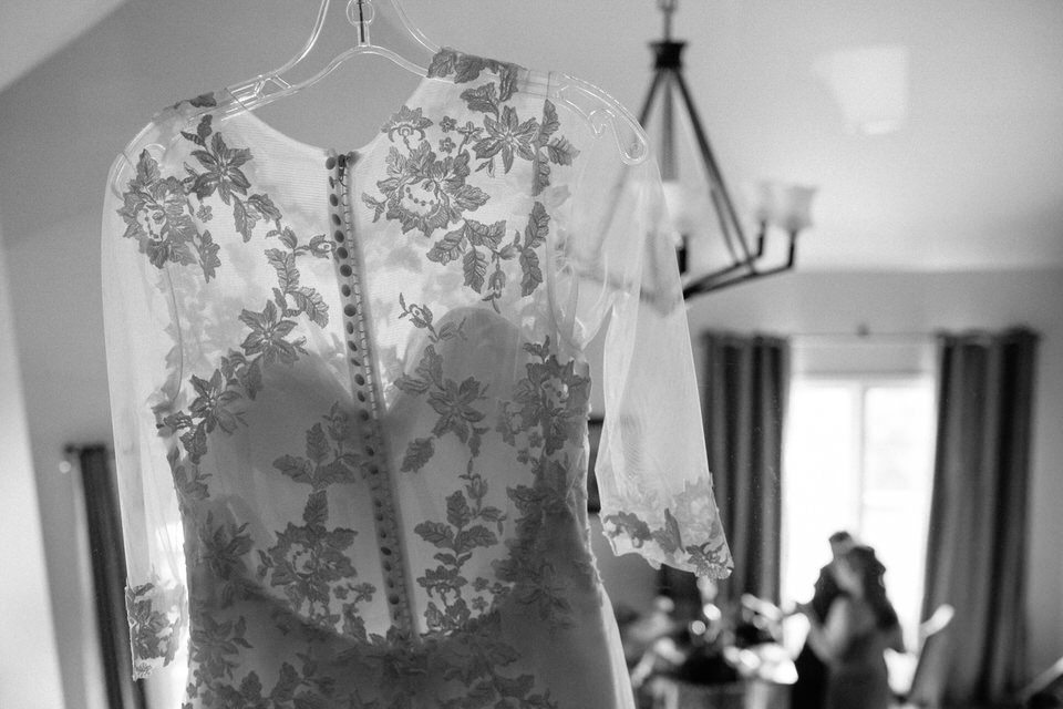 Lacy wedding dress hanging while bride gets ready in the background