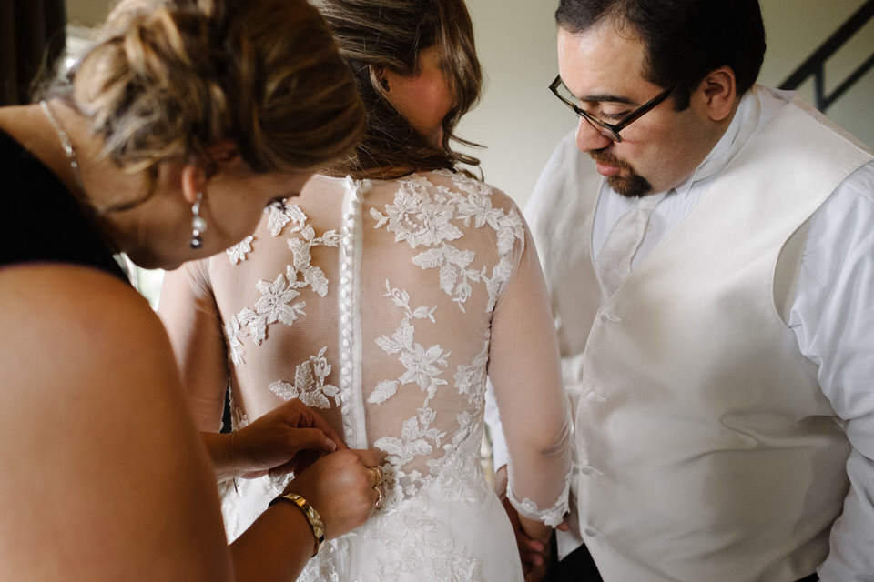 Bride's dress getting buttoned while groom looks on