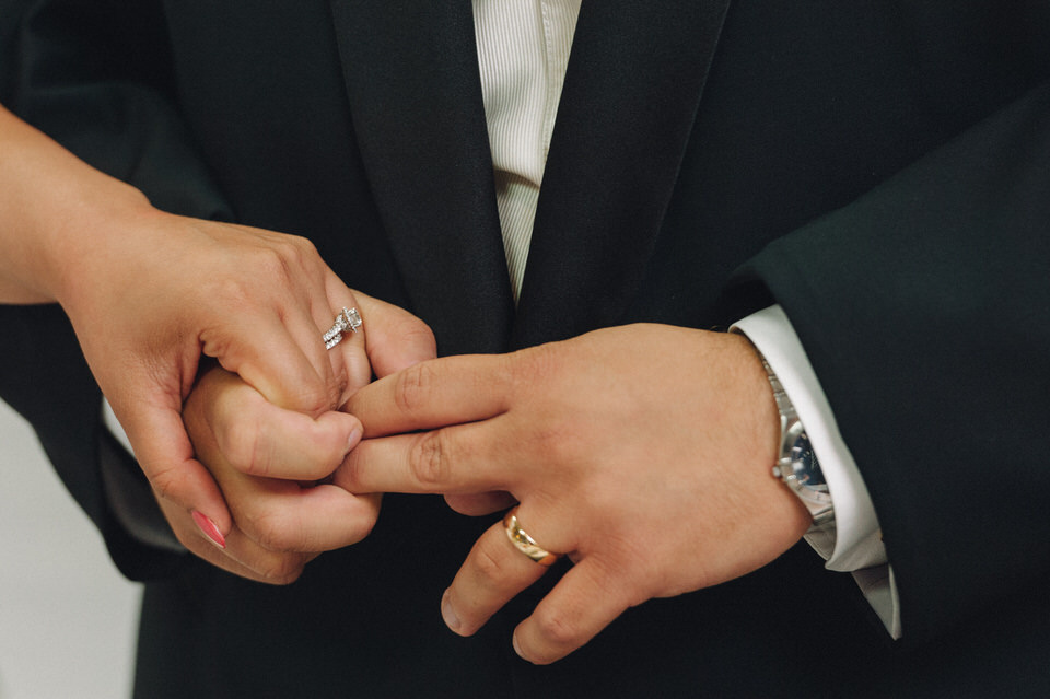 Close up of wedding couple holding hands with wedding rings