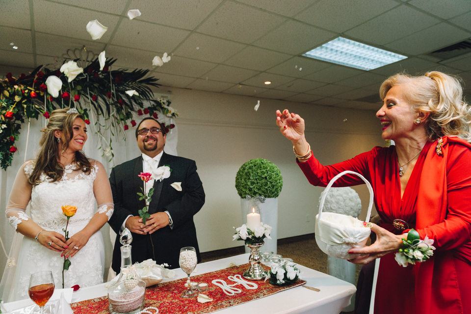Mother throwing petals and coins on bride and groom