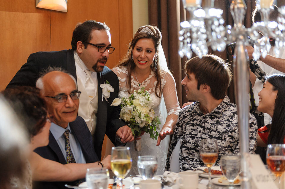 bride and groom chatting with guests at table