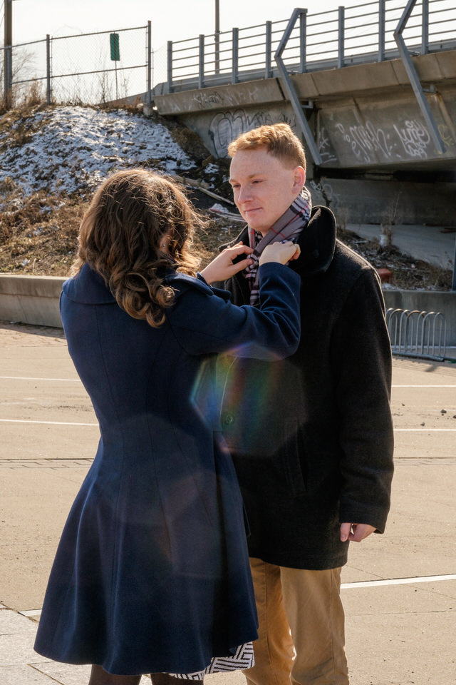 Engaged couple with coats in chilly engagement photo