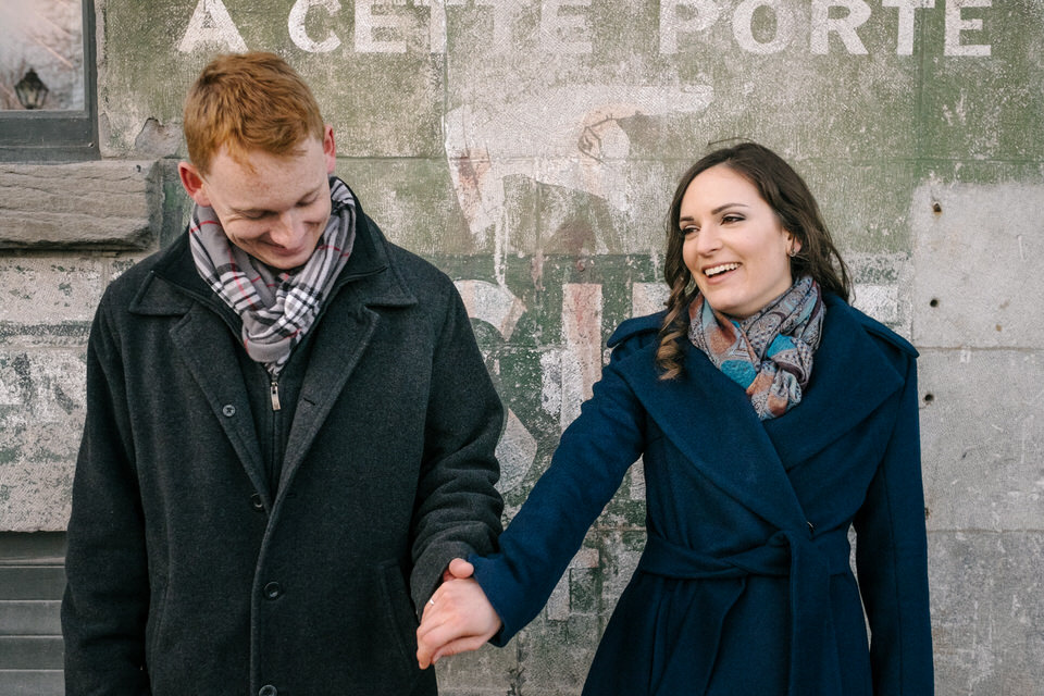 Couple holding hands in front of old wall