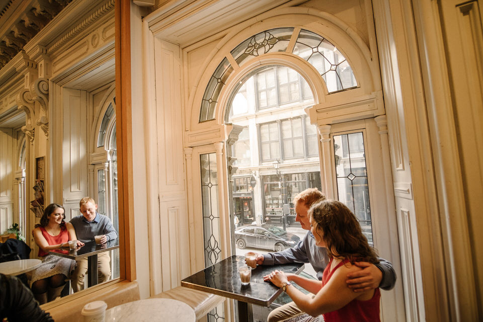 Engagement photo of couple enjoying coffee in Old Montreal