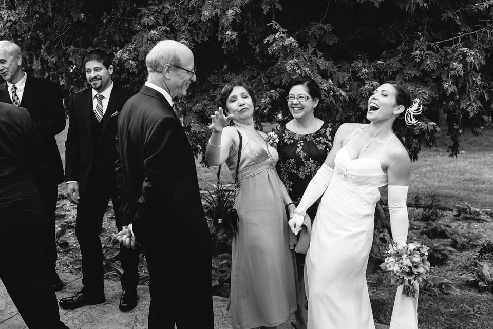 Wedding guests congratulating and laughing with bride