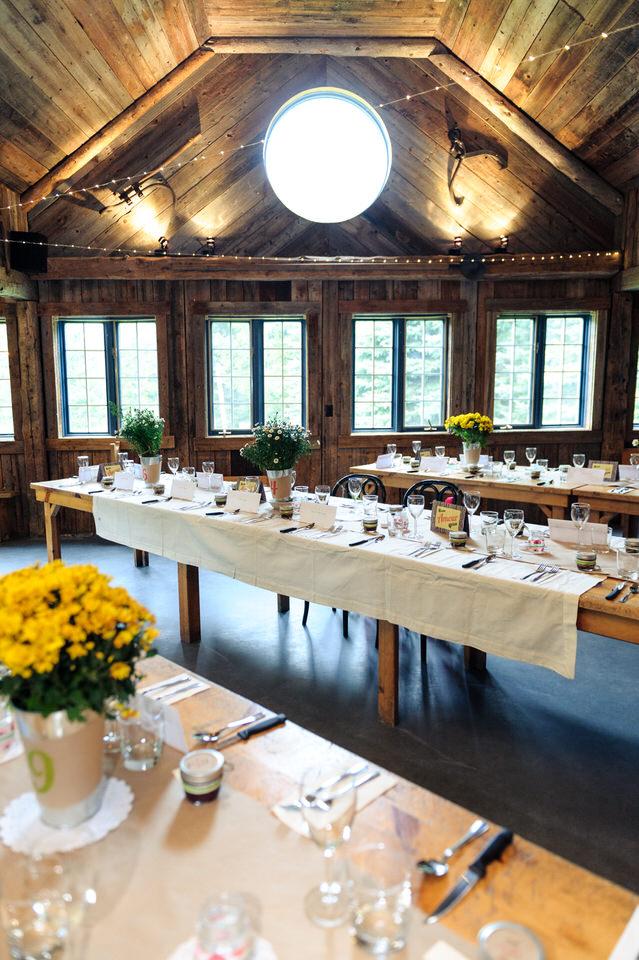 Tables longues installés pour un diner de mariage à l'intérieur de la Cabane à Sucre Haut-Bois Normand