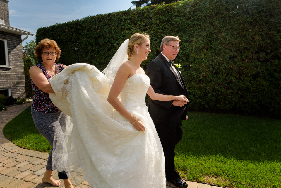 Bride leaving her house with her dad and a neighbour helping with her dress