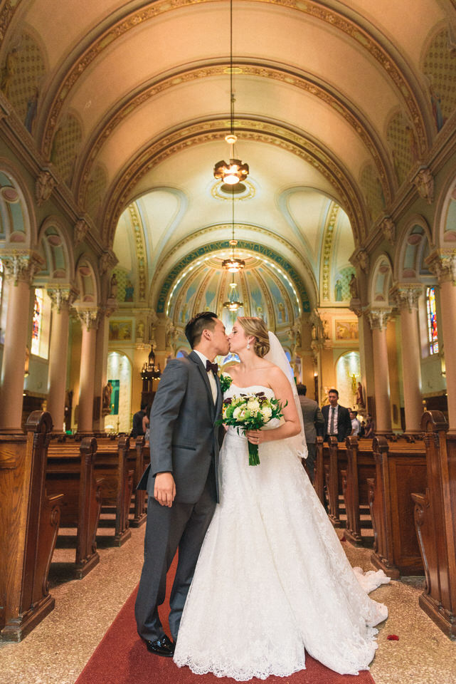 Bride and groom kiss as they walk back the aisle of a Catholic church in Lachine