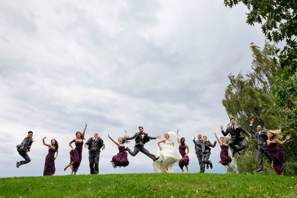 Wedding party jumping on a hill