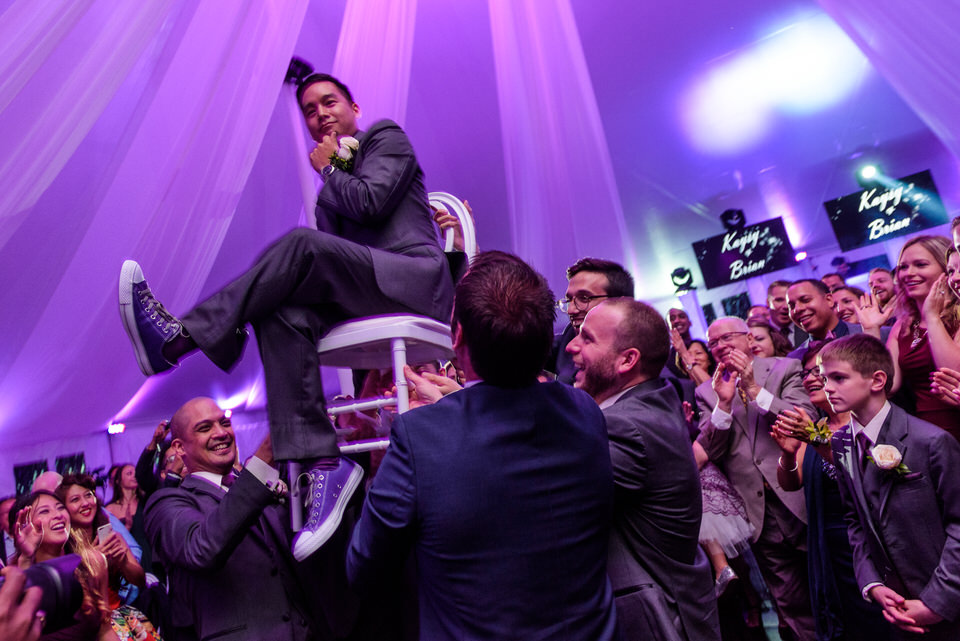 Wedding guests carrying groom on a chair