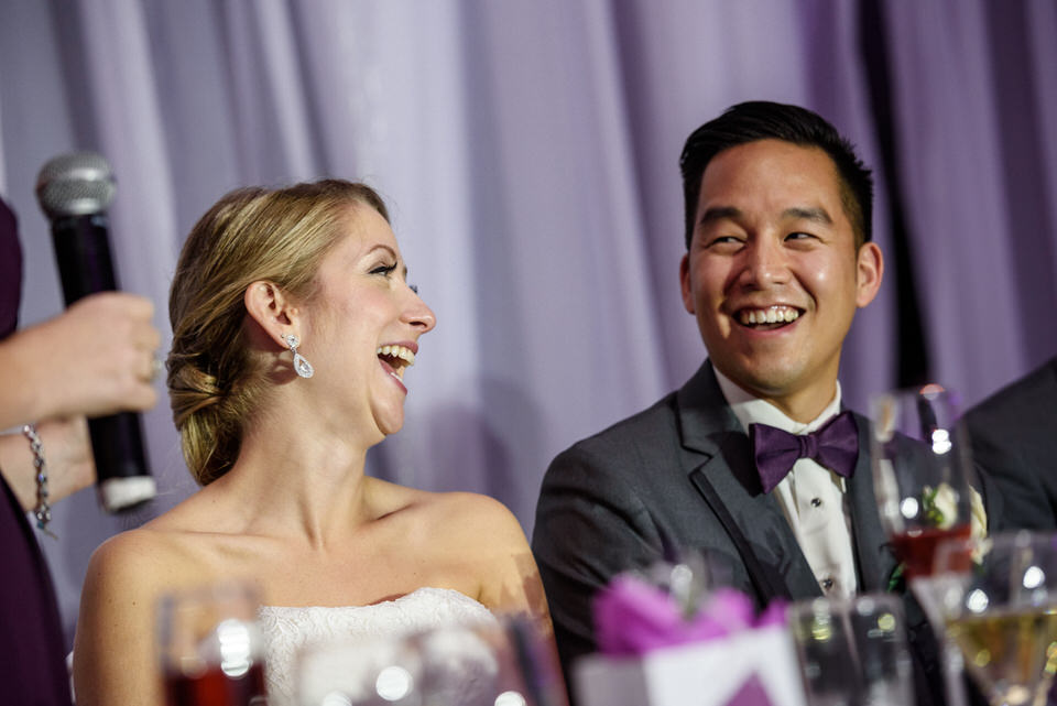Bride and groom laughing during wedding speech
